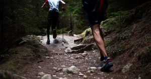 Two men running on a uphill trail in the woods for exercise.