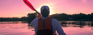 Man kayaking in a serene lake at sunset.