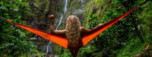 Woman in a tropical setting relaxing in a hammock looking at waterfalls.