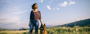 Woman with a dog in a field looking toward the sun on clear day.