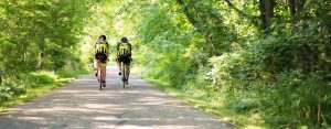 Two men riding bicycles down a bike path for exercise.